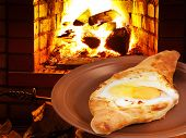 Hachapuri With Egg On Plate And Fire In Stove