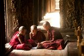 Three Young Monks Reading At Shwenandaw Monastery In Mandalay,Myanmar.