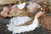 The wholemeal flour in scoops on wooden table on sackcloth background