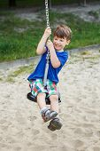 Boy Hanging On Swing Rope