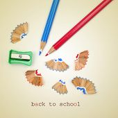 a sharpener, pencil crayons of different colors and the sentence back to school on a beige backgroun