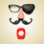 a funny face formed with fake mouth, nose and glasses with mustache and pirate patch on a beige back