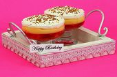 Happy birthday card with strawberry trifles on wooden tray with pink background