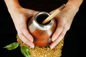 stock photo of calabash  - Woman hands holding calabash and bombilla with yerba mate isolated on black - JPG
