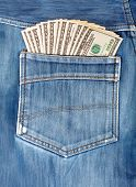 A Hundred Dollar Bills Sticking In The Back Pocket Of Denim Blue Jeans