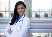 stock photo of multicultural  - Closeup portrait of friendly smiling confident female doctor healthcare professional with labcoat and stethoscope arms crossed - JPG