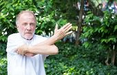 stock photo of hamstring  - Closeup portrait senior mature man in white shirt stretching arms isolated green trees background - JPG