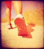 an athletic pair of legs running or jogging on a path during summer toned with a soft vintage instagram like filter