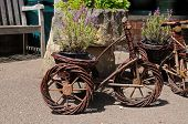 pic of tricycle  - Wooden tricycle plant pot holders Lower Slaughter Cotswolds Gloucestershire England UK Western Europe - JPG