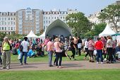 ST.LEONARDS-ON-SEA, ENGLAND - JULY 12, 2014: The audience sit on the grass at the annual St.Leonards