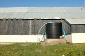 image of plinth  - A black plastic water storage tank with blue pipes against a wooden building with tin roof - JPG