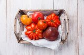 Ripe Fresh Colorful Tomatoes In Wooden Box On White Wooden Background