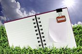Blank notebook on the Green Meadow and Blue Sky Background