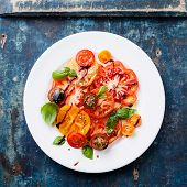 Ripe Fresh Colorful Tomatoes Salad With Olive Oil And Balsamic Vinegar On Blue Wooden Background