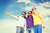 summer, holidays, vacation, happy people concept - group of male friends walking on the beach pointi