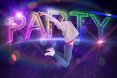 Cheerful young woman jumping against digitally generated colourful party text
