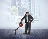 Mature businessman watering tiny businesswoman against urban projection on wall