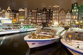 AMSTERDAM, NETHERLANDS - JULY 08: Amsterdam canal with traditioal houses and tour boats. Seeing Amst