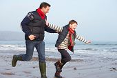Father And Son Running On Winter Beach