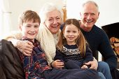 Portrait Of Grandparents Sitting On Sofa With Grandchildren