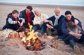 Multi Generation Family Sitting By Fire On Winter Beach