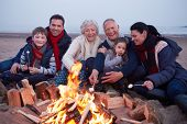 Multi Generation Family Having Barbeque On Winter Beach