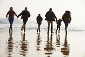 Multi Generation Family Walking On Winter Beach