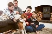 Family Relaxing Indoors And Stroking Pet Dog