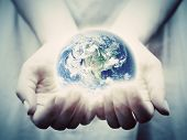 The earth shines in young woman hands. Concepts of save the world, protection, taking care, environm