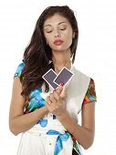 Beautiful brunette holding two playing cards, isolated on white