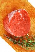 raw red meat : fresh beef single fillet chop with thyme on wooden plate . isolated over white backgr