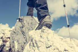 stock photo of follow-up  - Close up of hiking shoes and trekking poles ascending a mountain - JPG