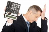 Depressed mature businessman holding a calculator.
