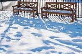 Abandoned Wooden Benches In Snowy Garden With Footprints