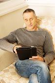 Contemporary mature man using digital tablet indoors.