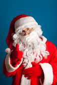 Santa Claus with red costume pointing by finger