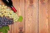 Red wine bottle and bunch of grapes on wooden table background with copy space