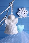 Knitted Christmas angel hanging on bud on color wooden background