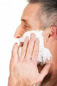 Side view of a man applying shaving foam.