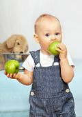 One year old kid eats a green apple.