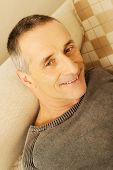 Smiling mature man lying on a sofa at home.