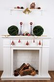 Fireplace with Christmas decoration on wooden floor near white background