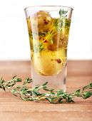 Green olives in oil with spices and rosemary in glass on wooden table