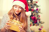 Beauty girl with Christmas gift box at home. Christmas Gift. Happy Surprised Girl opening Gift box. Pretty young woman in Santa hat portrait. Christmas Tree