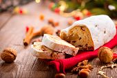 Christmas Stollen. Traditional Sweet Fruit Loaf with Icing Sugar. Xmas holiday table setting, decorated with garlands, baubles, wallnuts, hazelnuts, cinnamon sticks. Warm colors toned.