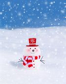 Cute snowman outdoors in snowy weather, traditional winter decoration, little smiling snowman wearing red hat and scarf, Christmas greeting card