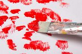 Close Up Of Paint Brush With Red Paint Strokes Over White