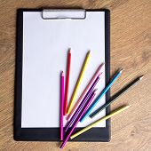 Colored Drawing Pencils And Clipboard With Blank Paper On Wooden Table