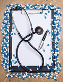 Heal Of Tablets, Clipboard, Stethoscope And Pen On Wooden Table