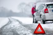stock photo of breakdown  - warning triangle with winter car breakdown in background  - JPG